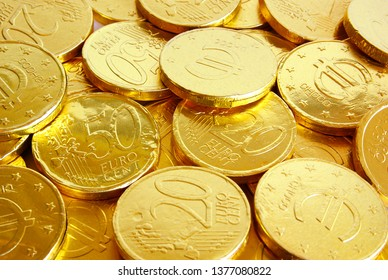 Pile of chocolate coins wrapped in shiny golden tinfoil