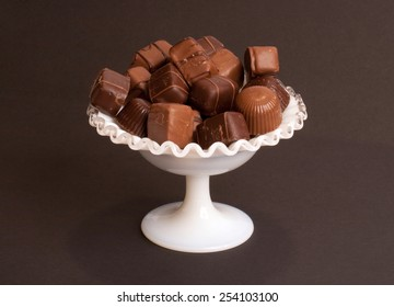 A pile of chocolates in a white dish.