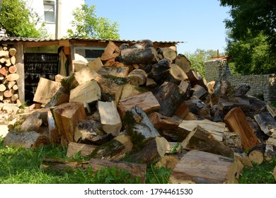 A pile of chopped dry firewood lies near the woodpile. Preparation of firewood for the winter. Background from dry chopped firewood. They prepare firewood for heating in winter.