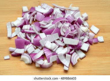 pile of chopped red onion on wood background