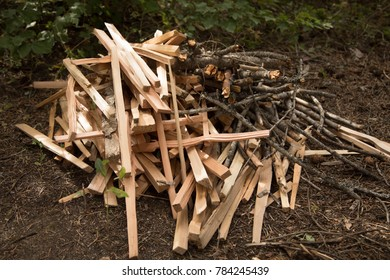 Pile of chopped wood kindling, beside a stack of broken branches for a campfire