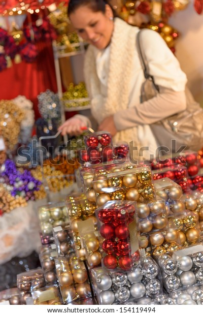 Pile of Christmas balls in plastic boxes woman shopping