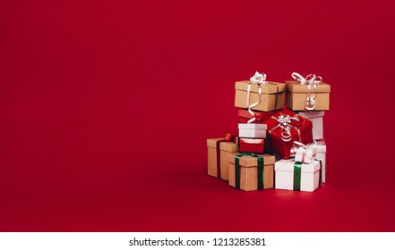 Pile of christmas gift boxes isolated on a red background. Colorful gift boxes tied with ribbons and bows.
