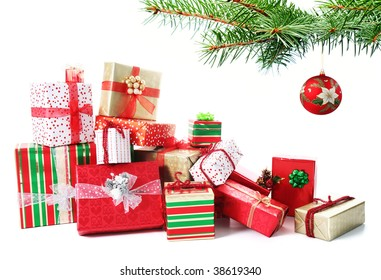A pile of Christmas gifts in colorful wrapping with ribbons under a Christmas tree..
