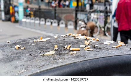 Pile of cigarette butts and ash stubbed out on the top of a black litter bin (trash can) in a busy city street. Numerous stubs and filters have just been left in a pile on the top in full view.