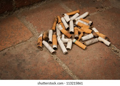 A pile of cigarette butts littering a brick walk.