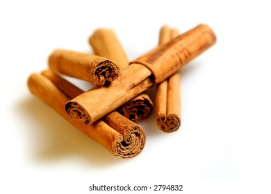 A pile of cinnamon sticks on a white surface, with natural shadow.