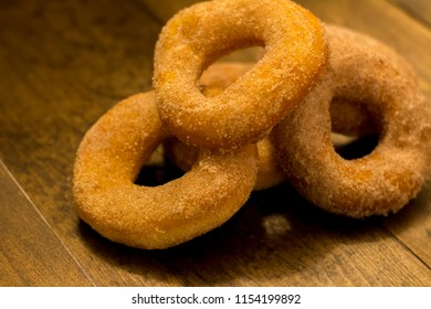 A pile of cinnamon sugar cake donuts on wooden table against a dark background