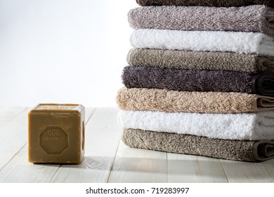 Pile of clean soft and fluffy towels folded with sustainable Marseille olive oil soap over a white natural wooden background for sustainable bath, green washing laundry and healthy body care, studio