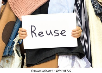 Pile of cloth with Reuse table sign in woman's hands. Take care of the environment. Waste recycling and nature conservation.