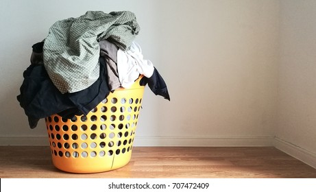 Pile of clothes in broken orange colored plastic laundry basket indoors