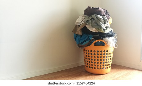 Pile of clothes in broken orange plastic laundry basket with clothes hanger.