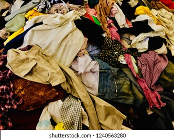 Pile of clothes. Closeup of a pile of different used clothes on sale in a flea market. Different colored clothes background. Mixed up dresses, jeans, skirts and other used clothes
