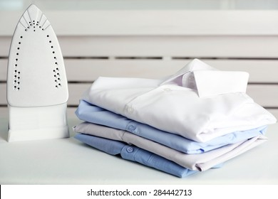 Pile of clothes and electric iron on wooden background