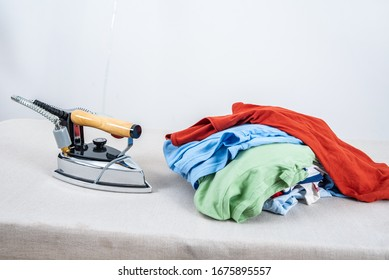 A pile of clothes and irons that need to be ironed on the table