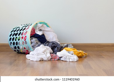 Pile of clothes overflow plastic laundry basket for washing preparations. Household chores concept
