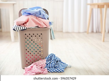 Pile of clothes in plastic laundry basket indoors