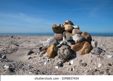 pile of coarse stones on the beach of the baltic sea against the blue sky built by tourists, copy space