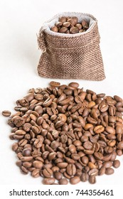 Pile of coffee beans and jute drawstring bag on the white background.