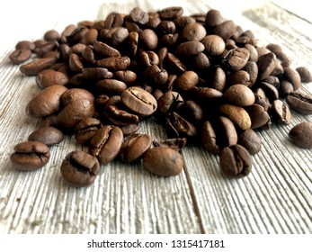 Pile of coffee beans on a wooden surface