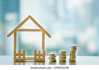 Ein Haufen Münzen zerbricht. Mini-Holzhaus und Reihe von Münzen fällt. Hypotheken- und Immobilienanlagen oder Versicherungsfinanzierungs- und Anlagekonzept.