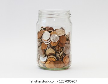 A pile of coins in a glass jar on white background. Piggy bank with money.