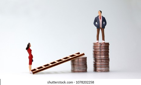 The concept of gender discrimination between employed and paid in the workplace. A pile of coins and miniature people.
