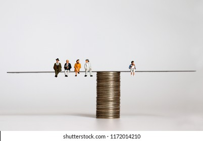 A pile of coins and miniature people. A concept of population aging and relative birth rates.
