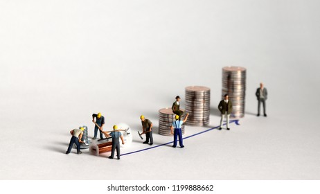 The pile of coins and miniature people. A concept of production and income distribution.