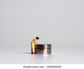A pile of coins and a miniature woman. The concept of women in economic poverty.