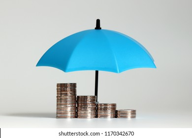 A pile of coins and open blue umbrellas.