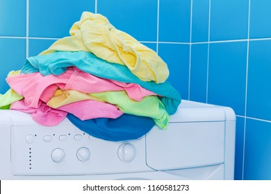 Pile of colored clothes on top of washing machine at bathroom, laundry concept of color cleaning