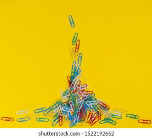 a pile of colored paper clips scattered on a yellow surface