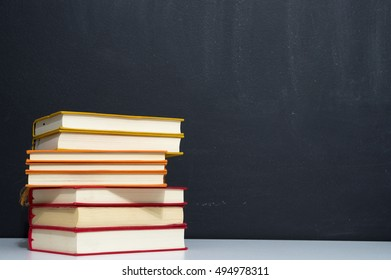 pile of colorful books on blackboard background