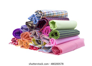 Pile of colorful checkered plaid fabric roll on a white background