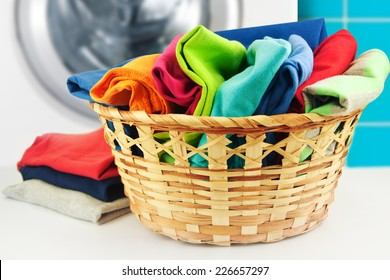Pile of colorful clean clothes with washing machine.