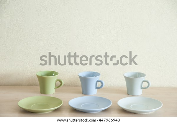 Pile of colorful coffee cups on wooden table with the dishes for prepare serve.