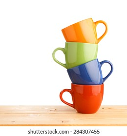 Pile of colorful cups on wooden table isolated on white background