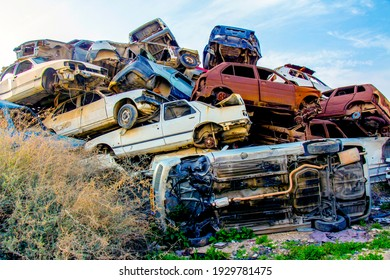 Pile of colorful discarded cars on junkyard