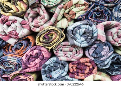 Pile of colorful fabric clothes stack on ground