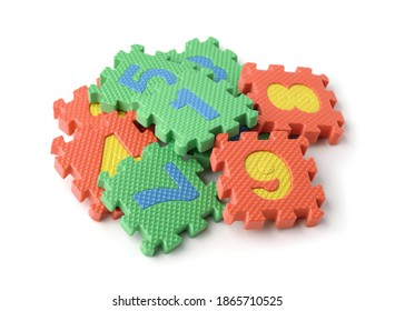 Pile of colorful foam math numbers puzzle pieces isolated on white