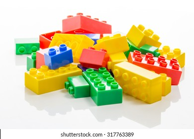 Pile of colorful plastic building bricks on white background