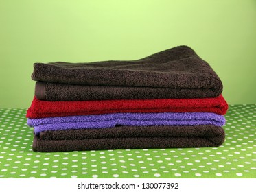Pile of colorful towels, on  green background