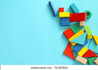 Pile of colorful toy blocks on blue background.