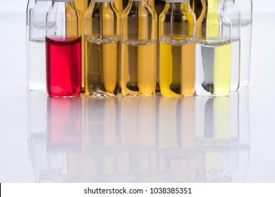 Pile of colorful transparent glass ampoules with liquid medicine isolated on an abstract white background. Healthcare, medical, pharmaceutical and beauty concept. Closeup with soft selective focus