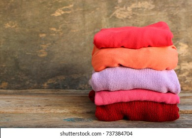 Pile of colorful warm clothes on wooden background. Toned image.