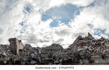 A pile of concrete gray debris of a destroyed building with a huge beam in the foreground against a blue sky with clouds. Panorama.