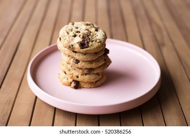 Pile of Cookies on a pink plate on a wooden table