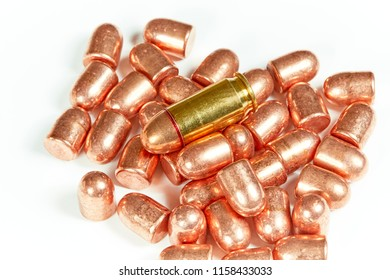 A pile of copper bullet heads with one cartridge isolated on white