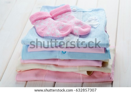 5787a06c4 Pile of cottony pastel baby clothes, patterned socks on the top, close-up